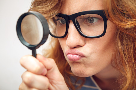 freaks: Young geek looking through magnifying glass