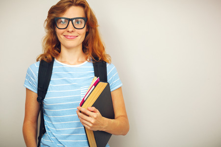 Portrait of Young smart student with books standing. photo