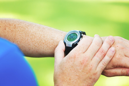 Male runner looking at his heart rate monitor. photo