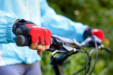 mountain biker: Closeup of hands in red protective gloves holding handlebar.