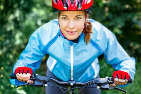 handlebars: Happy Young woman leaned over the handlebars of her bike. Stock Photo