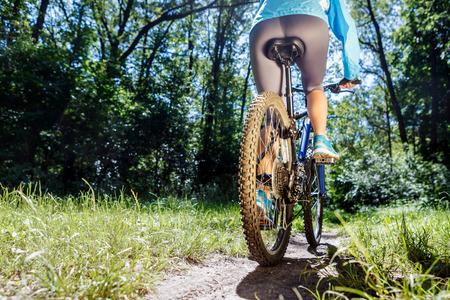 Young woman on mountain bike fast ride outdoors. 版權商用圖片