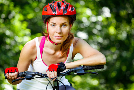 leaned: Happy Young woman leaned over the handlebars of her bike. Stock Photo