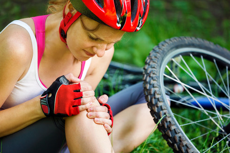 on hands and knees: Young woman fell off mountain bike.