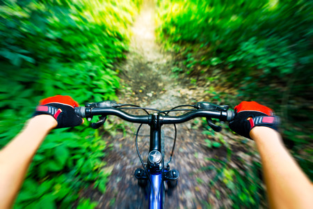 Mountain biking down hill. View from biker. Stock Photo