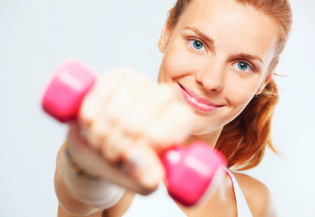 Young woman with dumbbells in her hands. photo