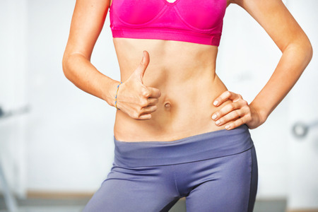 human stomach: Closeup of young slim woman with six-pack torso. Stock Photo