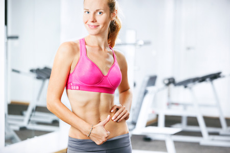 Portrait of happy athletic woman in gym showing thumb up. photo