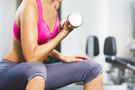 body pump: Young woman exercising with dumbbells in gym.