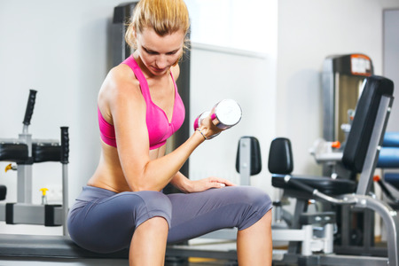 Young woman exercising with dumbbells in gym. photo