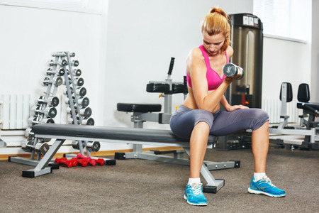 athletic body: Young woman exercising with dumbbells in gym.
