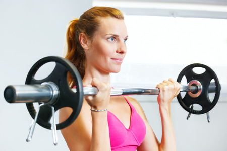 Young woman exercising with barbell in gym. photo