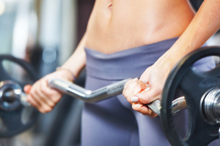 body care: Young woman exercising with barbell in gym. Stock Photo