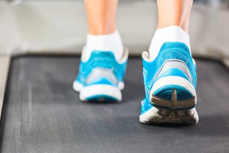 Vrouw lopen op de loopband in de sportschool.