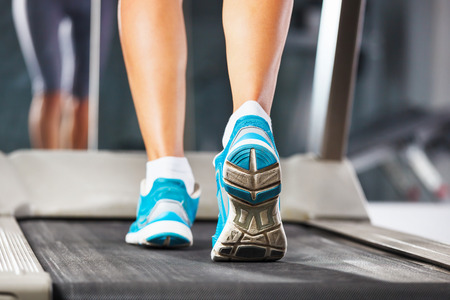 Woman running on treadmill in gym. photo