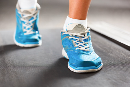 walking shoes: Woman running on treadmill in gym. Stock Photo