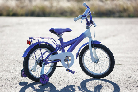 training wheels: Small kids bike with training wheels outdoors.