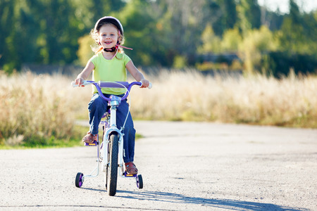 training wheels: Small funny kid riding bike with training wheels. Stock Photo