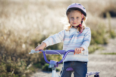 Small funny kid riding bike with training wheels. photo