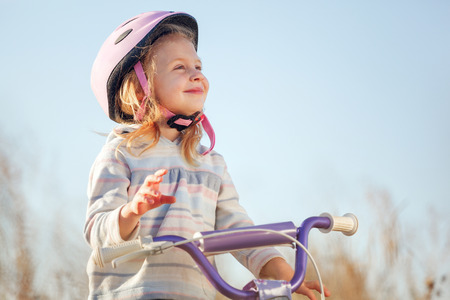 training wheels: Small funny kid riding bike with training wheels. Stock Photo