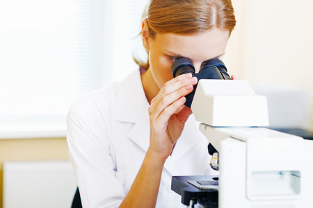 Beautiful woman in a laboratory working with a microscope.