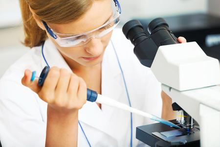 Mooie vrouw in een laboratorium werken met een microscoop. Stockfoto