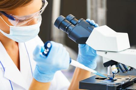 doctores: Mujer hermosa en un laboratorio que trabaja con un microscopio.
