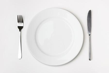 Messer, Gabel und Teller auf dem Tisch isoliert. Standard-Bild - 33198154