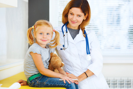 Portrait of pediatrician and little girl patient. photo