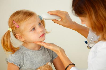 caucasian fever: Pediatrician taking temperature with professional thermometer.