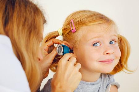 작은 girl`s 귀를 검사하는 소아과 의사.
