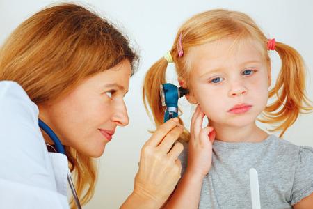 Pediatrician doctor examining little girl`s ears.