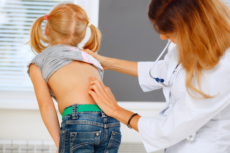 girls back to back: Pediatrician examining little girl with back problems. Stock Photo