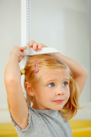 measure height: Portrait of little girl measuring herself.