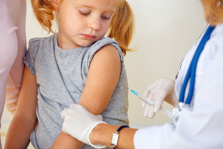 needle syringe infection: Doctor vaccinating small redhead girl.