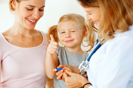 Doctor taking blood test from small patient. photo