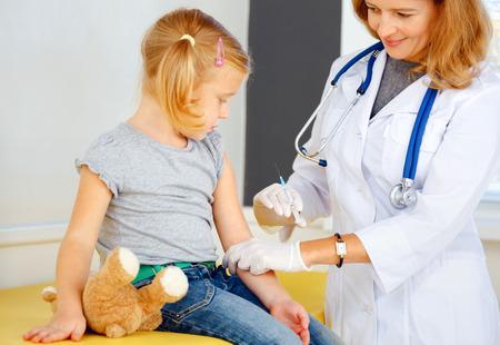 Arts vaccineren kleine roodharige meisje.
