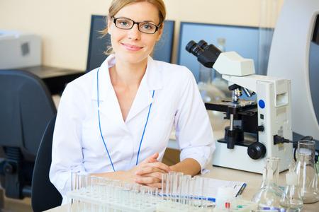 Portret van mooie jonge vrouw in een laboratorium zitten op haar werkplek te kijken naar de camera