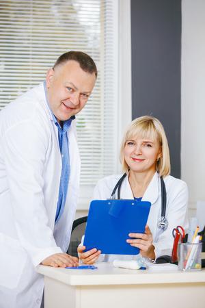 surgical coat: Portrait of two happy mature doctors. Stock Photo