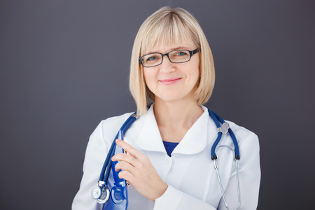 Portrait of confident doctor on gray background looking at camera. photo
