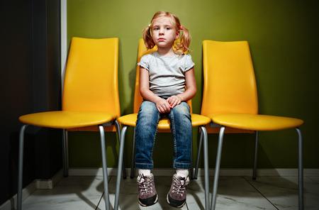 대합실에서 기다리고 작은 빨간 머리 소녀.