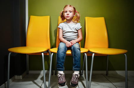waiting room: Little redhead girl waiting in reception room.