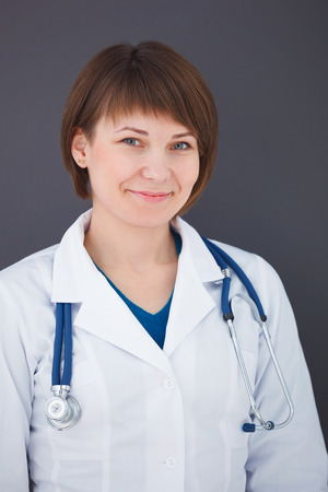 Portrait of happy young doctor on gray background looking at camera. photo