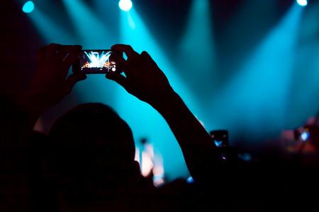 Mensen op concert schieten video of foto. Stockfoto
