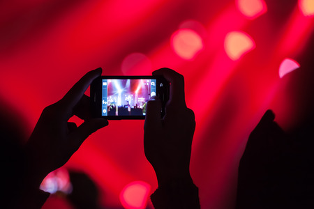 photo shooting: People at concert shooting video or photo. Stock Photo