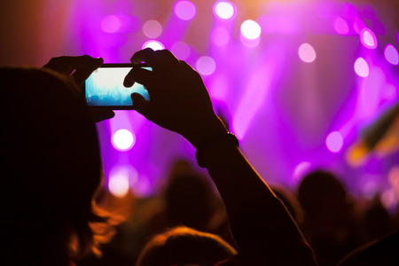 club scene: People at concert shooting video or photo. Stock Photo