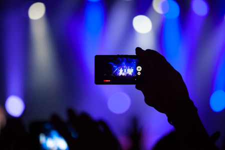 music band: People at concert shooting video or photo. Stock Photo