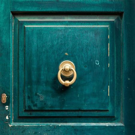 green door: Dark green wooden door panel with door knocker.