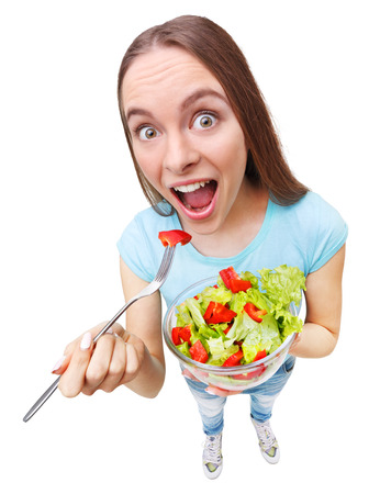 wide angle lens: Portrait of a fit healthy woman eating a fresh salad - wide angle lens effect.