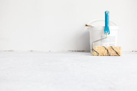 흰색 배경에 롤러 브러시와 양동이 페인트.